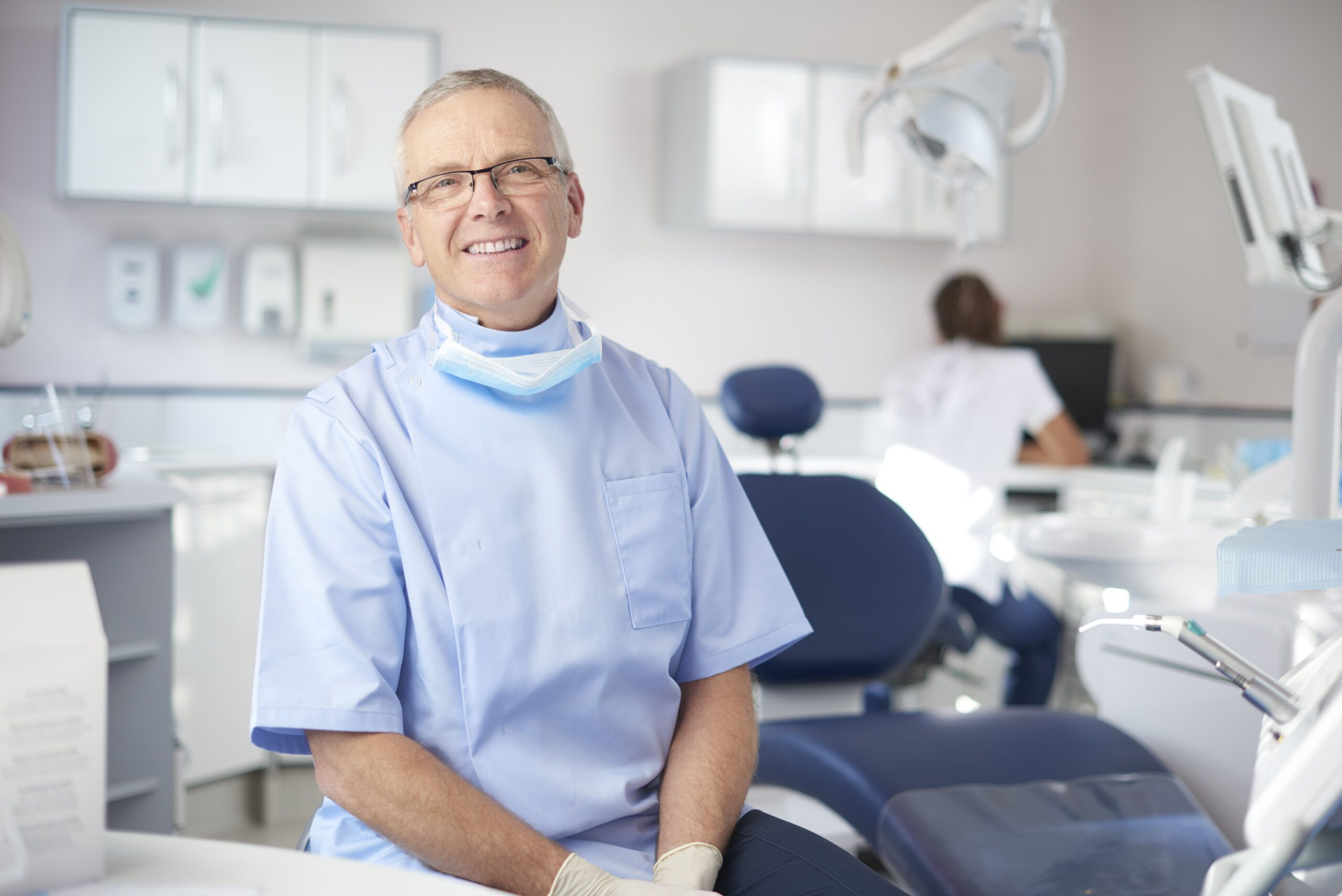 A mature male dentist is looking proudly to camera from his dentist's office. In the background a dental nurse is prepping for the next patient.